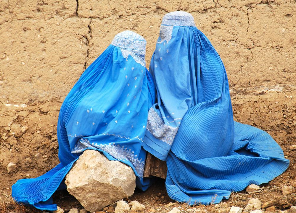 Afghan women sitting on the side of the road wearing blue burqas.