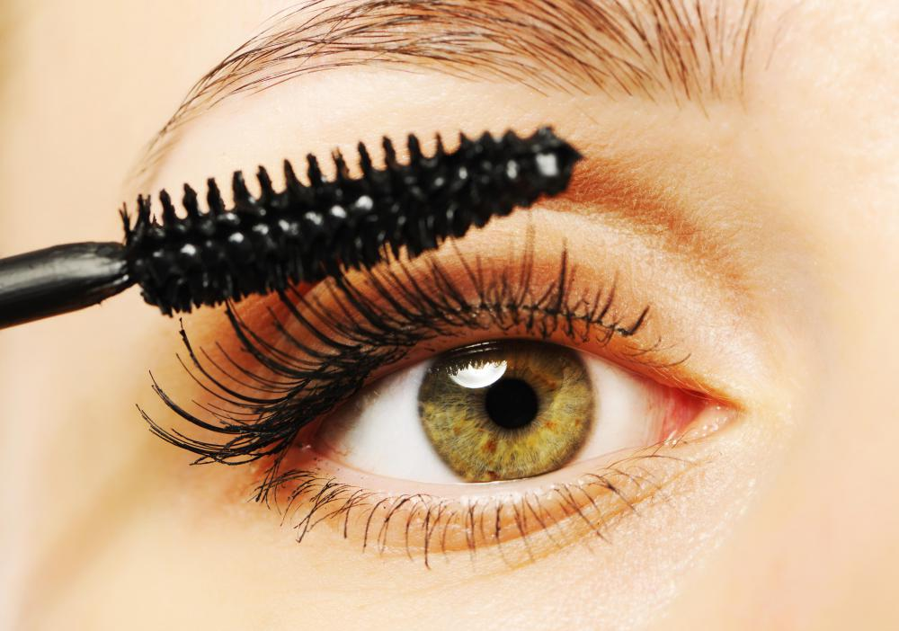 A woman applying mascara to her eyelashes.