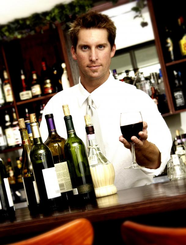 Bartender serving a glass of wine.