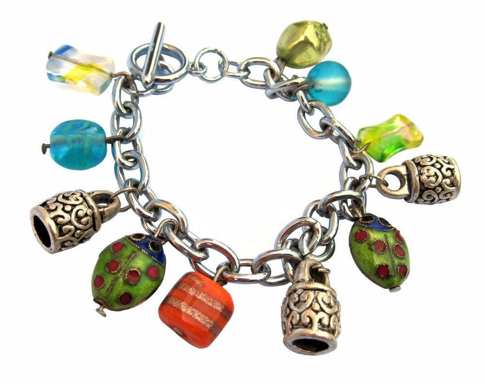A charm bracelet with tiny ladybugs and other small, colorful charms.