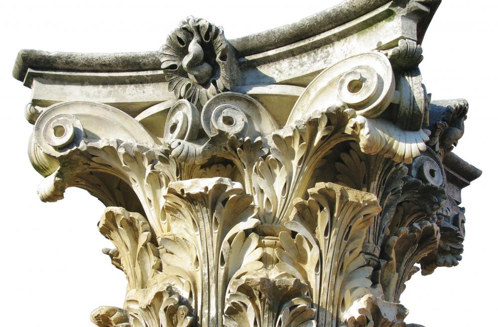 A Corinthian capital has an elaborate design that includes Ionic volutes and floral elements.