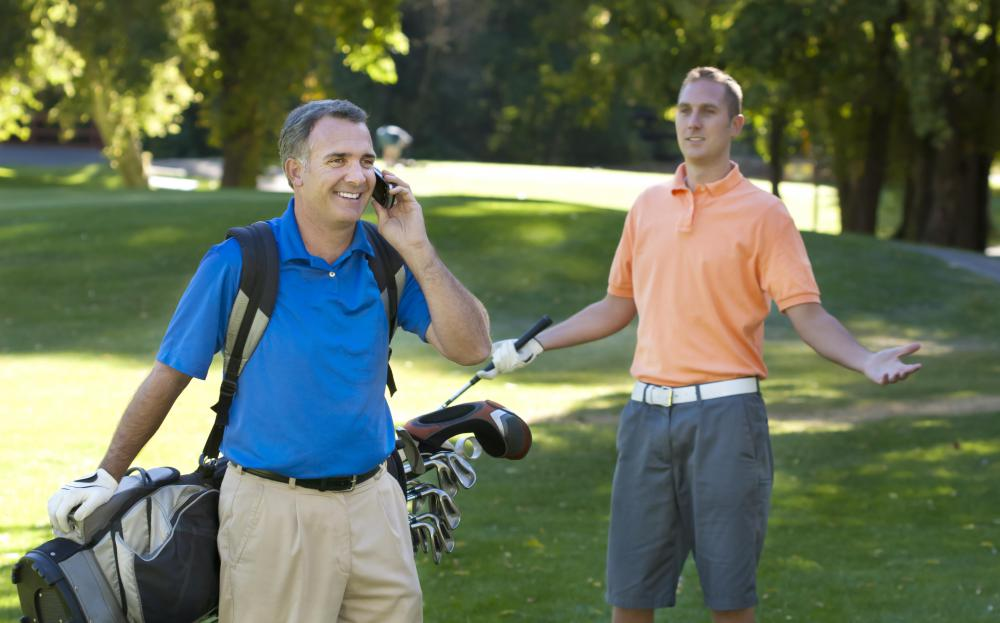 Golfer using a cellphone while on a golf course.
