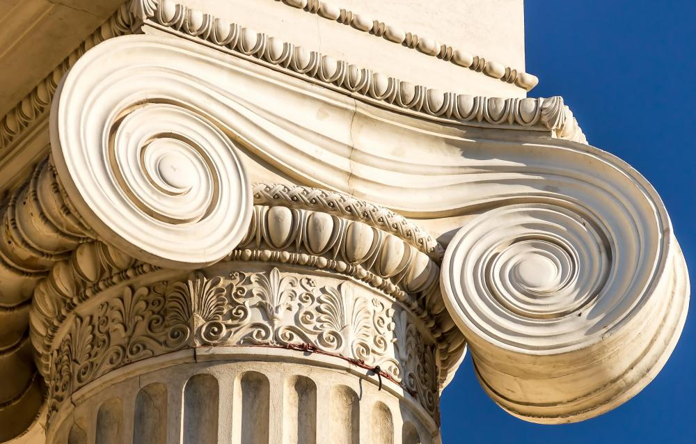 An Ionic capital is characterized by its spiraled scroll design, called volutes.