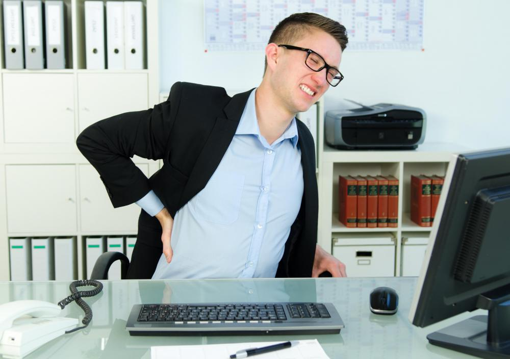 Long periods of sitting at a desk with poor posture can cause back pain.