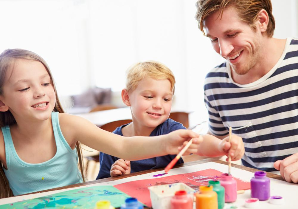 Children may use paint to decorate the box of a puppet theater.