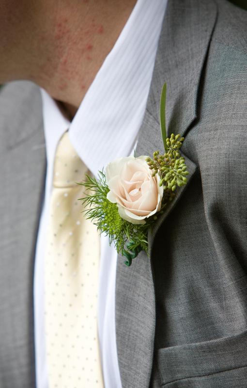 Grooms may wear a boutonniere, or a male version of a corsage, on their wedding day.