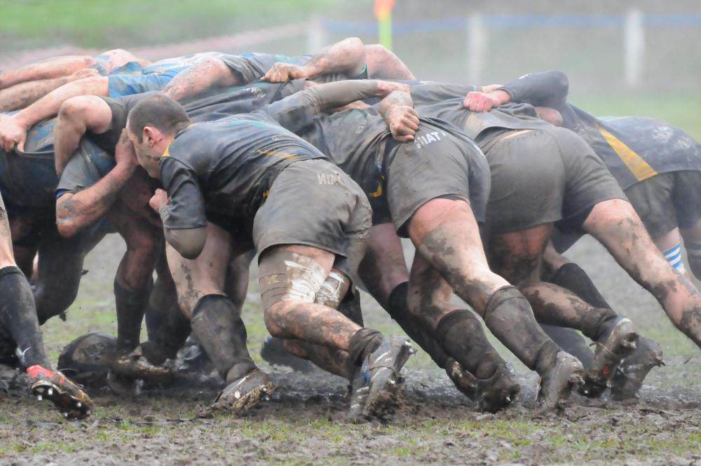 Muddy rugby scrum.