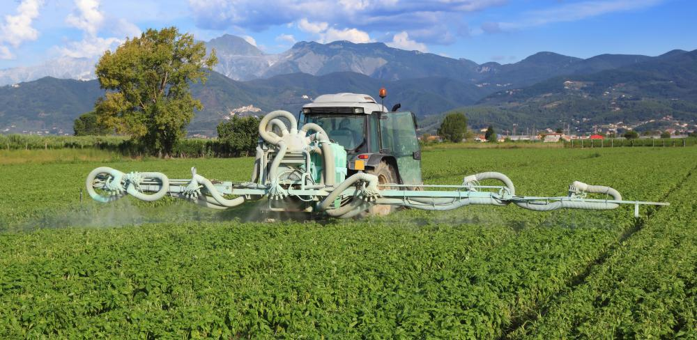 Tractors can have many uses when attached to other equipment, such as pesticide spray machines.