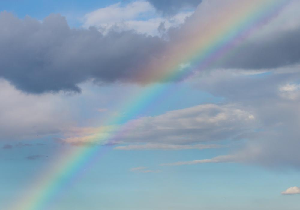 Water droplets in the atmosphere act like prisms when they bend, or refract, light and create a rainbow.