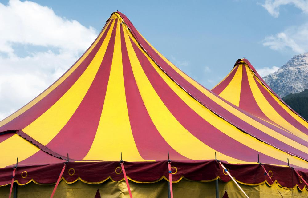 The classic setting for a circus is under a brightly colored tent.