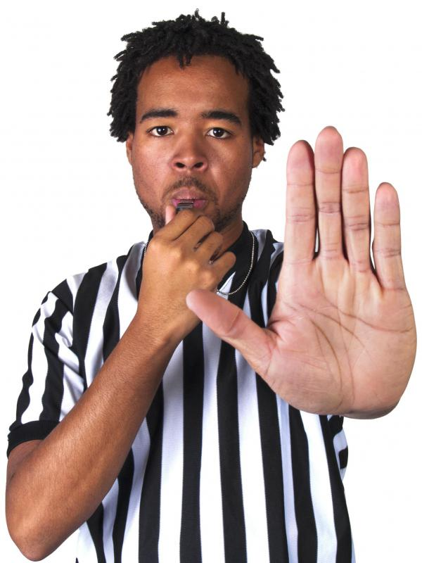 A soccer referee may use hand signals to indicate a ruling.