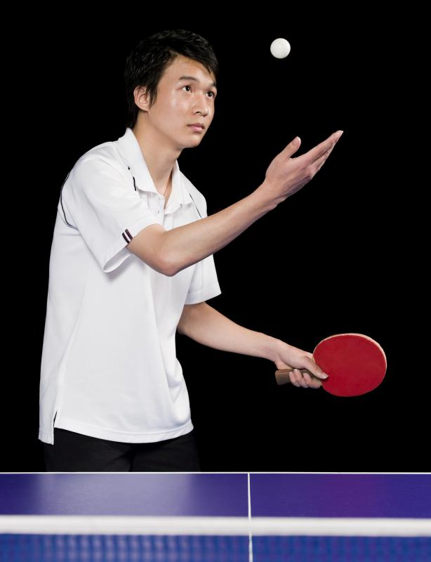 Table tennis player serving the ball.