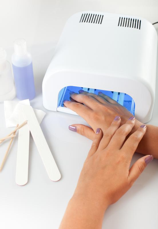 Gel nails curing under a UV light.
