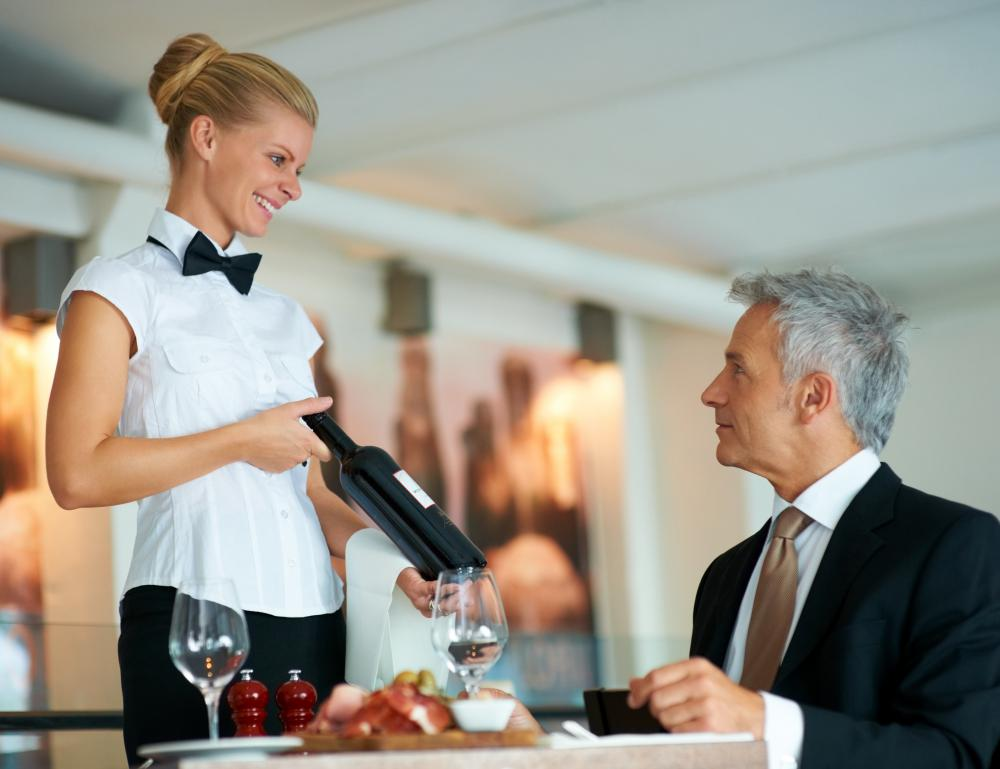 A hostess may introduce a restaurant's wine list to patrons.