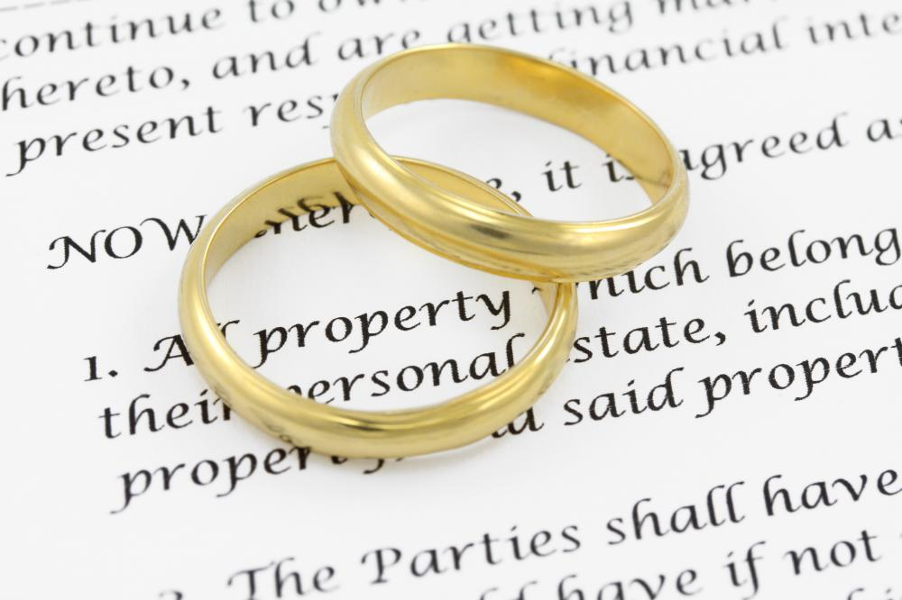 Wedding bands atop a marriage contract excerpt.
