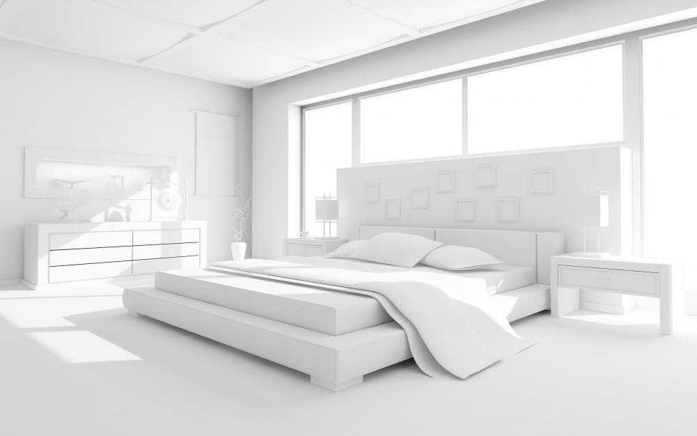 White bedroom with a bed with king size sheets.