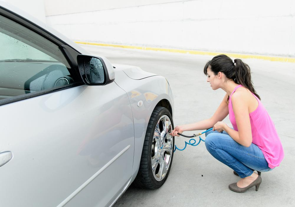 A woman filling her tires up with air and testing their air pressure.
