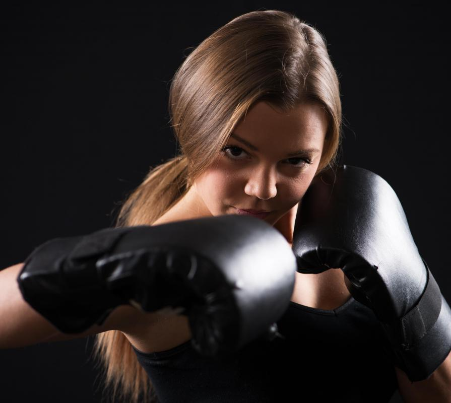 A self defense classroom is commonly stocked with boxing gloves and mats.