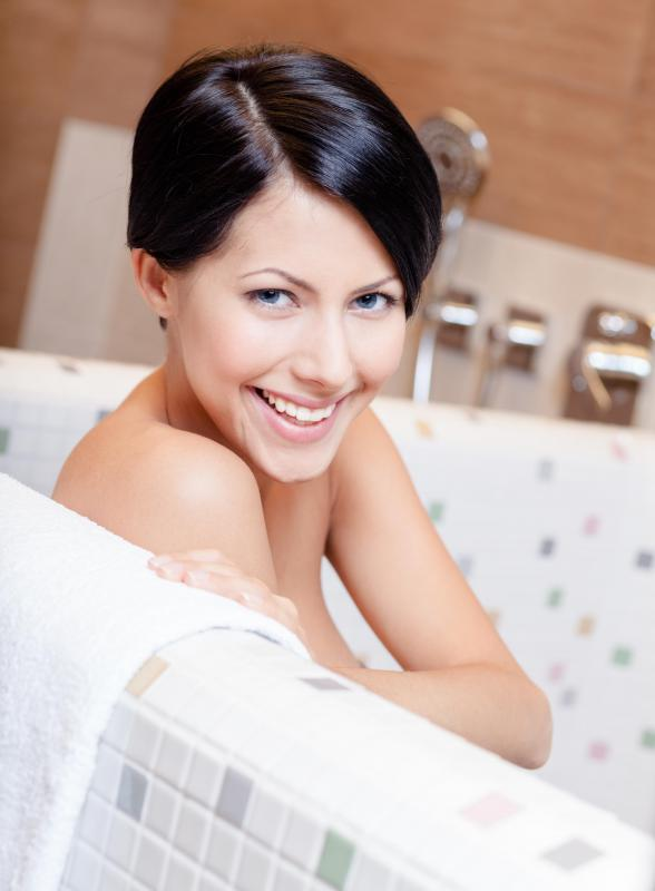 People with dry skin often smooth on hydrating moisturizer after a bath or shower.
